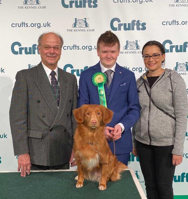 "Richard Paquette, CKC Junior Handling Chairperson, Isaac Clark, Canada's              Representative, with Nova Scotia Duck Toller ""Izzy"" Tivalake Easy to Love with Owner Miss Nicky Nevers"